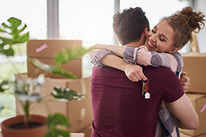 couple hugging holding keys surrounded by moving boxes