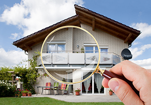 Magnifying glass in front of a home help by someone