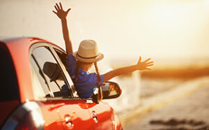 happy child girl goes to summer travel trip in car